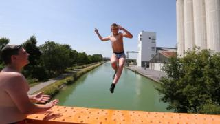 A teen jumps in Reims canal on June 25, 2019 correct thru a heatwave