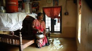 A woman stands in her flooded home