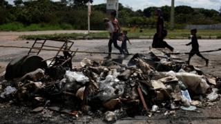 Venezolanos frente a tiendas de campaña quemadas en protesta el sábado