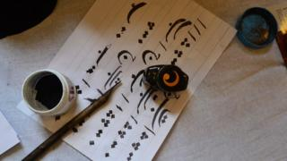 Ink, pen and paper with Arabic calligraphy