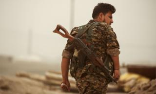 A member of the Kurdish People's Protection Units (YPG) walks with a Kalashnikov assault rifle slung behind his back in the town of al-Karamah, 26km from Raqqa, on 10 May 2017