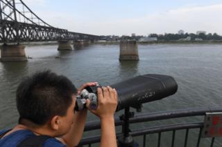 丹東鴨綠江邊一名男子利用公共望遠鏡眺望朝鮮新義州(5/9/2017)