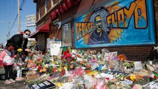 Una donna e dei bambini hanno deposto fiori in un memoriale di fortuna in onore di George Floyd, dove è stato arrestato, a Minneapolis, Minnesota, Stati Uniti.