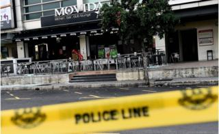 The exterior of the restaurant in Puchong district, outside Kuala Lumpur, on 28 June 2016, showing shattered glass on the floor and a line of police tape in the foreground.