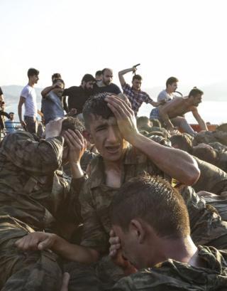 Civiles golpenado militares en el fondo de la foto y en el frente soldados jóvenes ocn el rostro en las manos en señal de desesperación