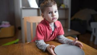 A child holding out a plate