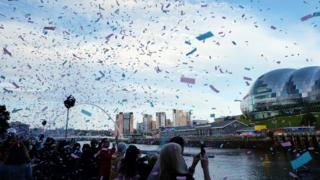 Tickertape falls from the sky on Newcastle Quayside as crowds line the bank