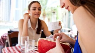 Девушки расплачиваются в кафе