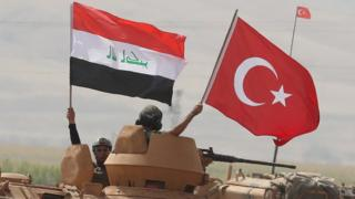 Soldiers hold Turkish and Iraqi national flag during a joint military exercise near the Turkish-Iraqi border (26 September 2017)