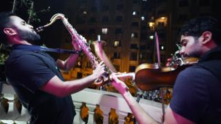 Mahmoud Saad (L) plays saxophone and Mohamed Adel (R) violin on their balcony during curfew in Giza, Egypt - Wednesday 1 April 2020