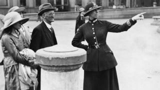 A female British Metropolitan Police officer points as she gives directions to a family of visitors from out of town, London, 1920s.