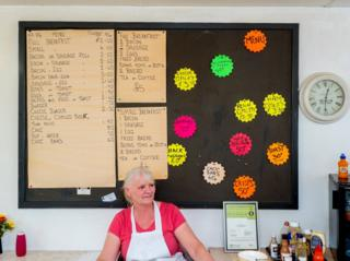 Babs sat under the menu board in BABS cafe. Blyth, Nottinghamshire.