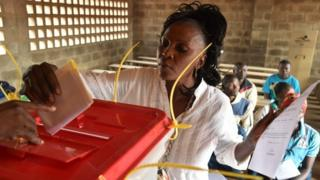 A woman casts her vote at a polling station on December 30, 2015 as people go to the polls to take part in the country's presidential and legislative in the Muslim district in¨PK5 in Bangui