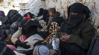 Women and children who fled the Islamic State (IS) group's embattled holdout of Baghouz wait in the back of a truck in the eastern Syrian province of Deir Ezzor