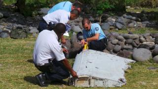 Police inspect a large piece of plane debris which was found on the beach in Saint-Andre, on the French Indian Ocean island of La Reunion. Photo: July 2015