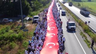 Thousands of supporters hold a long Turkish national flag on the march to Istanbul