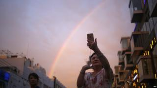 A Chinese woman takes a selfie with her mobile phone in front of a rainbow in Beijing, China on 3 August 2015