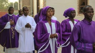 Worshippers in purple gowns