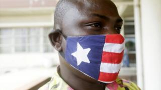 A man wears a mask decorated in the colour and pattern on Liberia's national flag on 27 April.