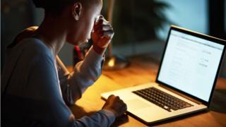 Mulher preocupada em frente a um computador