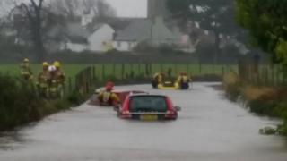 Firefighters rescue a woman from a car stuck in floods in Beaumaris, on Anglesey