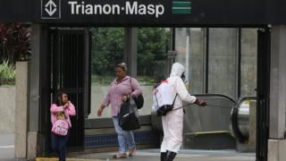 Workers wearing protective clothing clean the entrance to a subway in Sao Paulo