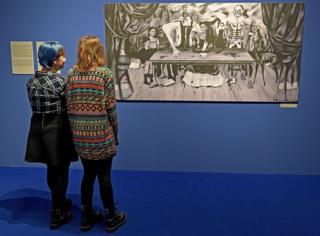 """Dos mujeres miran la réplica de """"La mesa herida"""" de Frida Kahlo en el Centro Cultural ZAMEK, en Poznań, Polonia."""