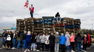 Woman surround the loyalist bonfire at Avoniel Leisure Centre