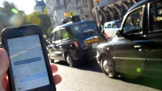 A Smartphone displays the Uber app with black cabs visible in the background