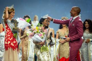 New Mrs Gabon dey laugh, as di master of ceremonies wear her crown back for head after e be fall for ground for Mrs Universe beauty pageant wey happen on Sunday. Gwen Madiba na runner-up for di competition wey hold for Durban, and e dey open to women wey dey between 25 to 45 years, and wey get family, career and dey do charity work.