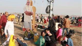 People sit near a cardboard cut-out of Narendra Modi