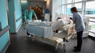 Nursing staff with patient on trolley