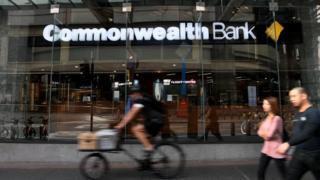 Pedestrians walk past a Commonwealth Bank branch