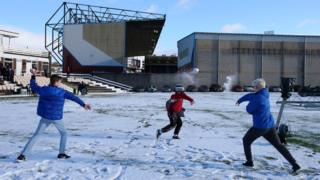 Fans play in the snow outside Turf Moor stadium ahead of Burnley and Southampton's Premier League game