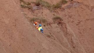 Coastguard crew rescuing a man and a woman from Filey Brigg in North Yorkshire