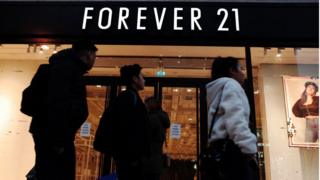 People walking past a closed Forever 21 store