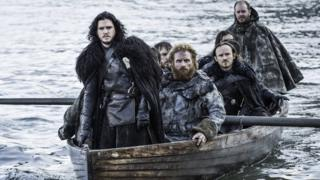 Jon Snow and other characters from Game Of Thrones travelling in a boat