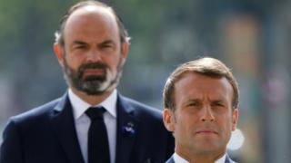 French President Emmanuel Macron (front) and French Prime Minister Edouard Philippe (L) attend a ceremony to mark the end of World War II at the Arc de Triomphe in Paris on May 8, 2020.