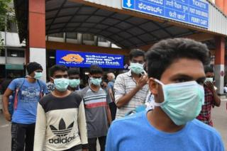 Young tourists wear facemasks as a preventive measure against the spread of the COVID-19 coronavirus outbreak at the Bangalore City Railway Station, on March 4, 2020.