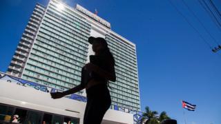 Imagem mostra mulher caminhando em frente ao Hotel Habana Libre, em Havana
