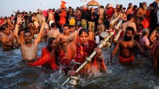 """امرأة هندوسية متدينة تحمل """"تريشول"""" وهي تغوص خلال أول """"شاهي سنان"""" (الحمّام الكبير)"""