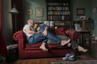 Portrait of a male couple on a sofa cuddling