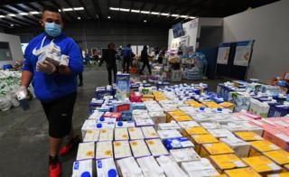 in_pictures A volunteer helps organise donated food supplies