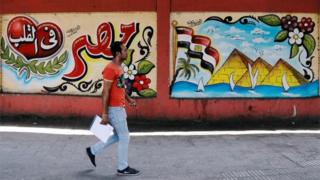 A man walks in front of graffiti in Cairo, Egypt - Monday 6 August 2018