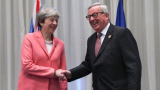 Theresa May and Jean-Claude Juncker smile and shake hands in front of the flags of their respective nations
