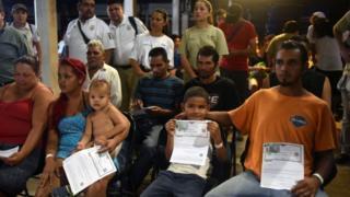 Migrantes centroamericanos sostienen su pase por razones humanitarias otorgado por las autoridades mexicanas.