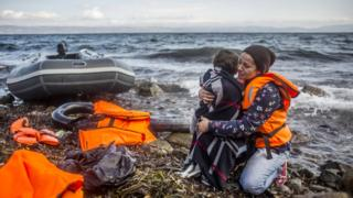 A woman holds her child as she arrived with other refugees on the shores of the Greek island of Lesbos