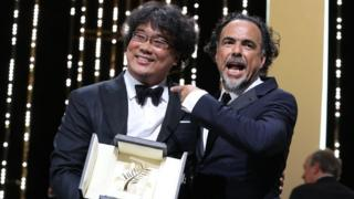 "South Korean director Bong Joon-Ho (L) poses on stage with Mexican director and President of the Jury of the Cannes Film Festival Alejandro Gonzalez Inarritu after he was awarded with the Palme d""Or for the film ""Parasite"" on May 25, 2019"