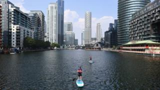 Paddleboarders off the Isle of Dogs, London, on Wednesday
