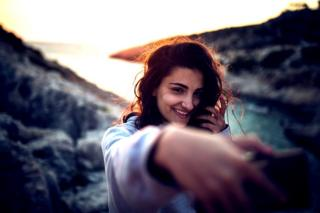 Mujer tomándose un selfie al atardecer.
